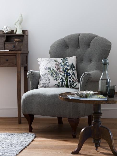 Sessel im Vintage Stil mit floralem Kissen neben einem runden Vintage Holzstuhl und einem Vintage Schreibtisch aus Holz