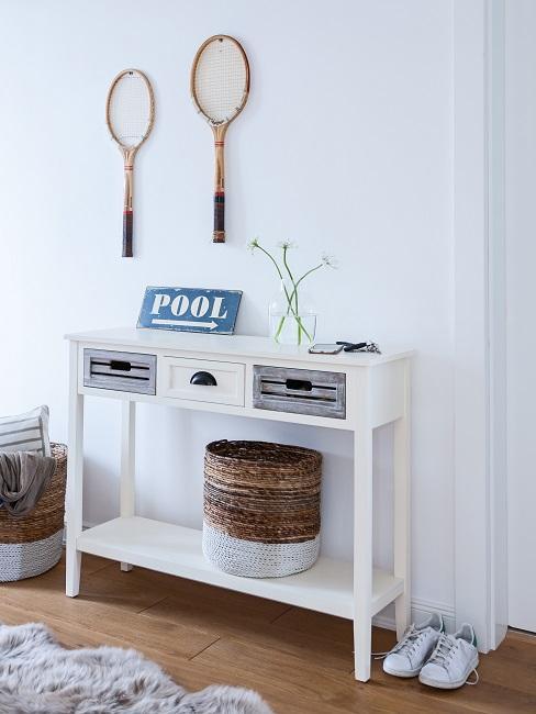 Weiße Konsole und Aufbewahrungskörbe, Tennisschläger aufgehängt als Flur-Wanddeko