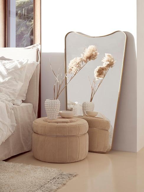 Helles Schlafzimmer in Naturfarben mit einem Samt-Pouf neben dem Bett, einem Spiegel an die Wand gelehnt und einer Vase mit getrockneter Blumendeko, davor ein Teppich in Beige