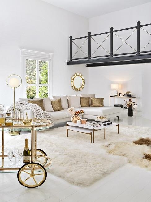 Großes und helles Luxus Wohnzimmer mit einem großen Sofa, einem flauschigen Teppich und Dekorationselementen in Gold