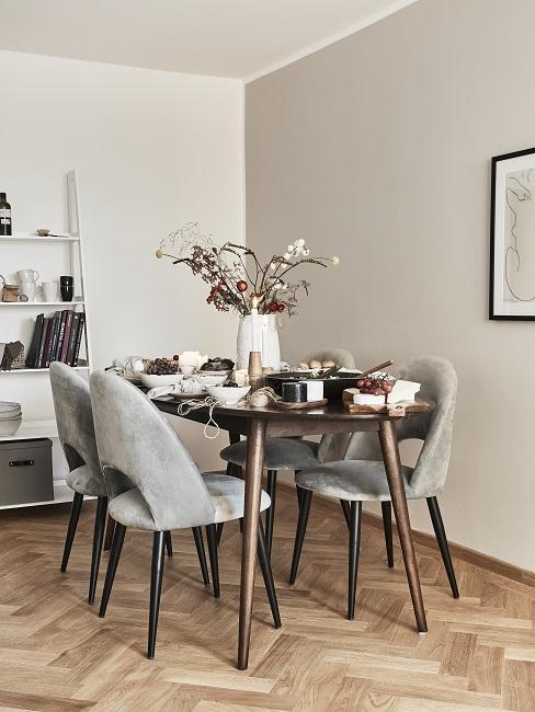 Esstisch aus hochwertigem Holz in einer Zimmerecke, dazu elegante Samtstühle in Hellgrau