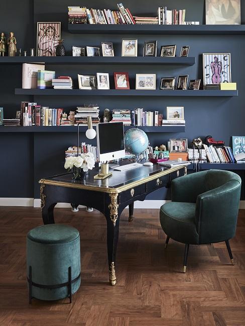 Wände in Petrol mit gleichfarbigen Wandregalen und vielen Büchern, davor ein luxuriöser Schreibtisch im barocken Stil mit einem Ledersessel und einem Samt-Pouf