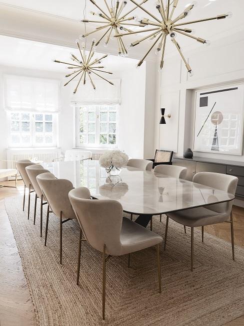 Esszimmer mit langer Tischtafel, Samtstühlen und drei stylischen Lampen als Hingucker