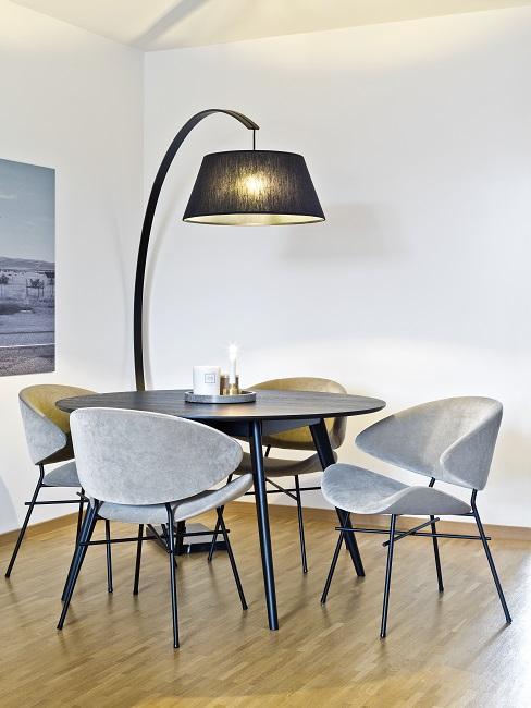 Minimalistische Raumecke mit einem runden Tisch und Samtstühlen, dazu eine Stehlampe, die den Tisch richtig beleuchtet