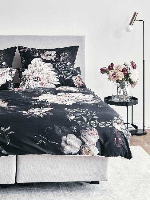 Schlafzimmer mit Bett mit geblümter Bettwäsche