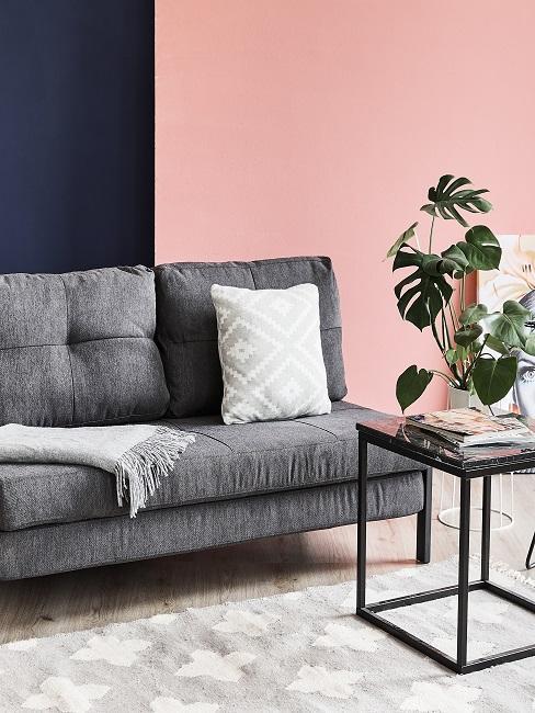 Wohnzimmer mit den modernen Wandfarben Dunkelblau und Rosa hinter einem grauen Sofa