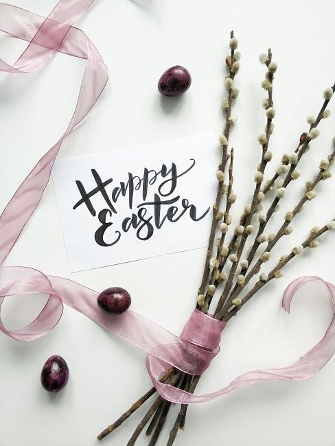 Mehrere Eichkätzchen Zweige mit einem Band zusammengebunden neben bemalten Ostereiern und einer selbst geschriebenen Ostergruß-Karte auf einem Tisch