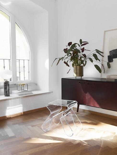 Lagom Wohntrend dunkles Sideboard aus Holz mit Pflanzen und Hocker aus Plastik