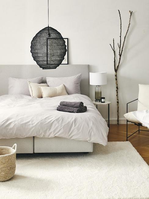 Lagom Wohntrend Schlafzimmer in weiß mit schwarzer Pendelleuchte, kleinem Beistelltisch, Deko-Ast, Sessel und Teppich