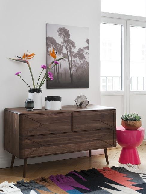 Stilmix Kubanisch mit Vontage Sideboard aus dunklem Holz, Dekovasen und Blumen, bunter Teppich und roter Hocker