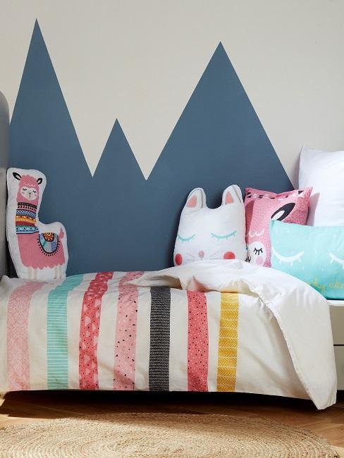 Kinderbett mit verspielten Kissen vor Wand mit blauen Bergen