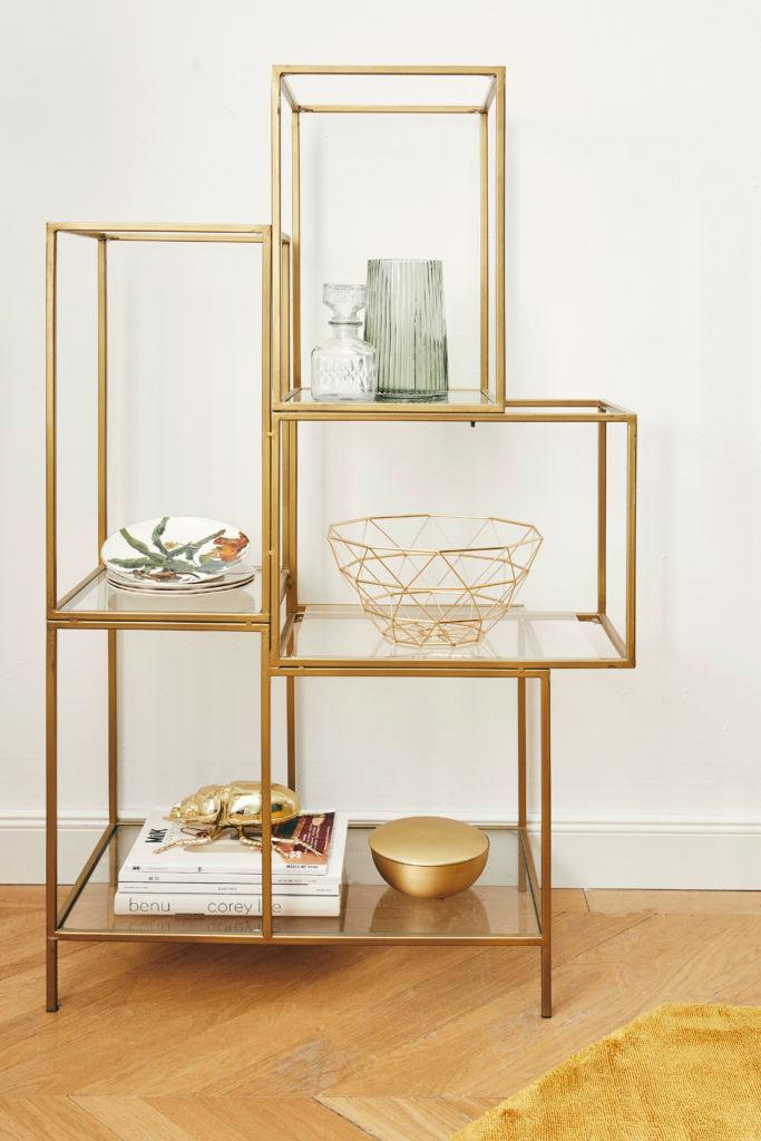 Goldenes Metallregal mit Deko Gruppen auf verschiedenen Ebenen angeordnet