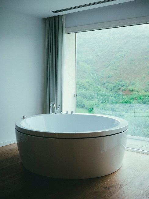 Runde freistehende Badewanne vor Fenster