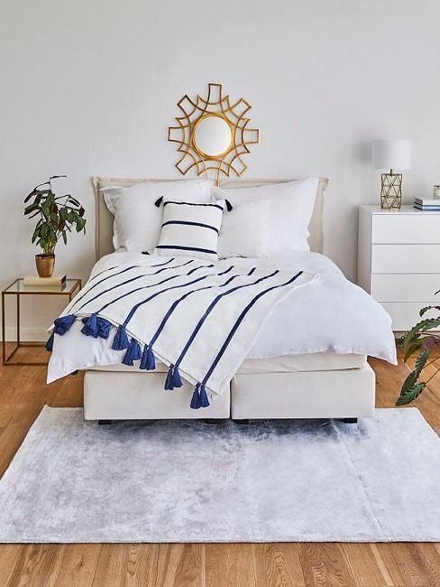 Maritimes Schlafzimmer mit weiß-blauer Bettwäsche und hellem Teppich