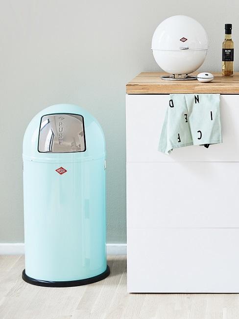 Blauer Mülleimer in der Küche neben weißer Küchenzeile