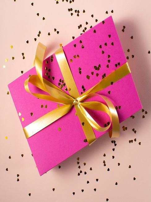 Verpacktes Geschenke vor rosa Hintergrund