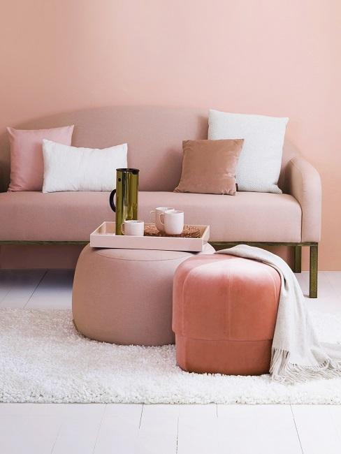 Wohnzimmer mit pastellrosa Wand, rosa Sofa, Poufs, Kissen und weißem Teppich