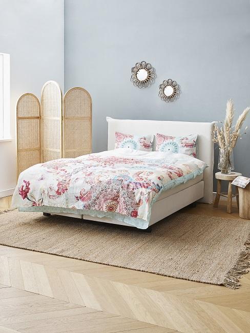Hellgraue Wandfarbe im Schlafzimmer mit bunter Bettwäsche und Accessoires aus Naturmaterialien