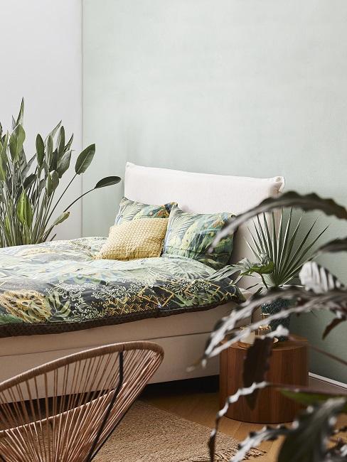 Helle Wandfarbe Grün im Schlafzimmer mit Pflanzen, grüner Bettwäsche und Holztisch