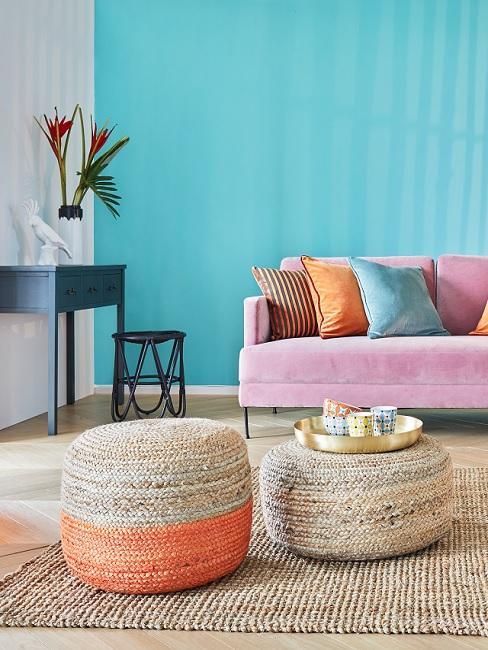 Wandfarbe Türkis im Wohnzimmer mit rosa Couch, Juteteppich und bunten Kissen