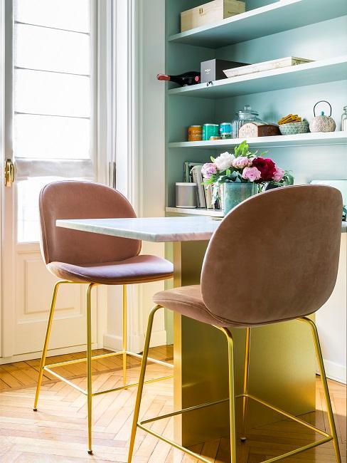 Türkisfarbene Wand in der Küche mit kleinem, weißen Tisch und rosafarbenen Samtstühlen