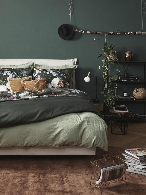 Dunkelgrüne Wand im Schlafzimmer mit Pflanzen, grüner Bettwäsche und braunem Teppich