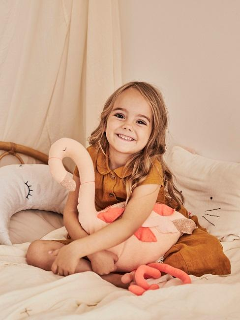 Mädchen sitzt auf Bett mit rosa Kuscheltier in den Armen