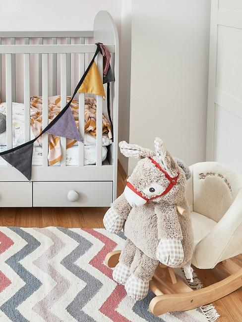 Babyzimmer mit gestreiftem Teppich und Schaukelpferd
