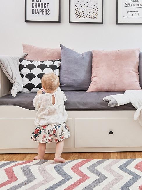 Baby steht an weißem Sofa vom Babyzimmer-Set