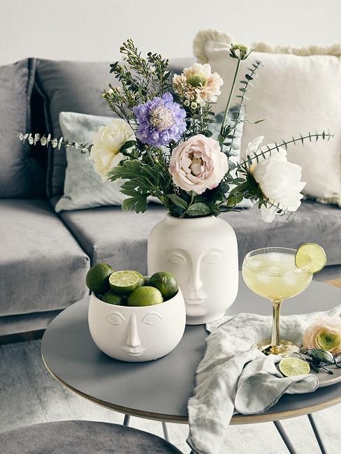 Blumenstrauß in Vase mit Gesicht auf Couchtisch