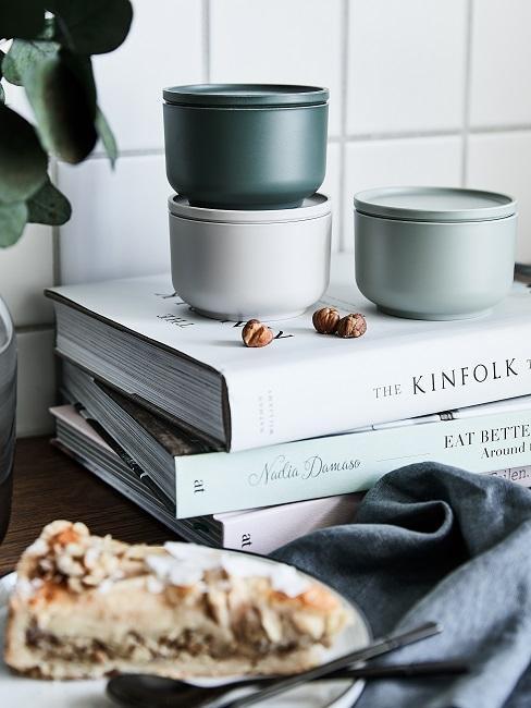 Bunte Aufbewahrungsdosen auf Kochbüchern als Küchendeko