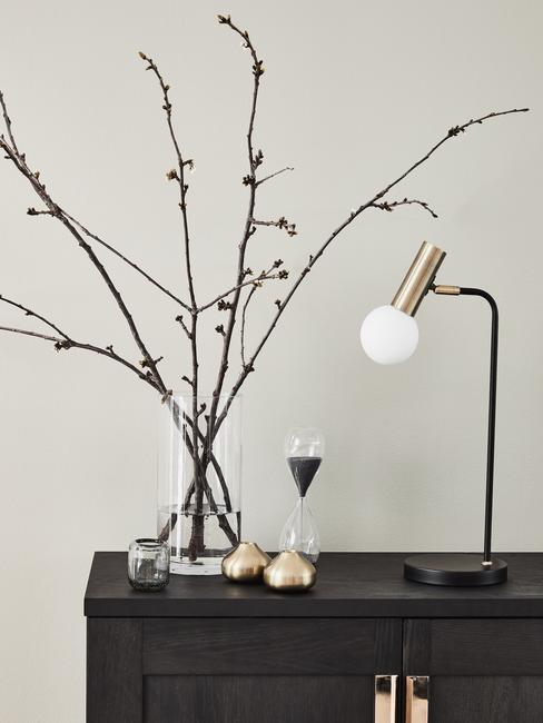 Cómoda negra decorada con ramas secas en jarrón transparente