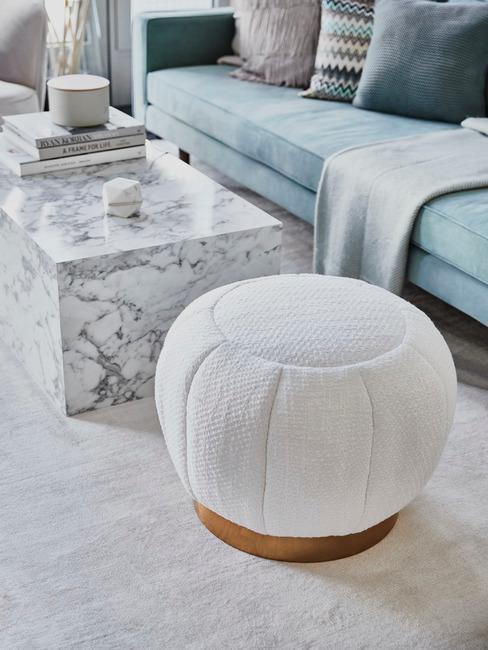 Mesa de mármol blanco con sofá azul claro y puf blanco
