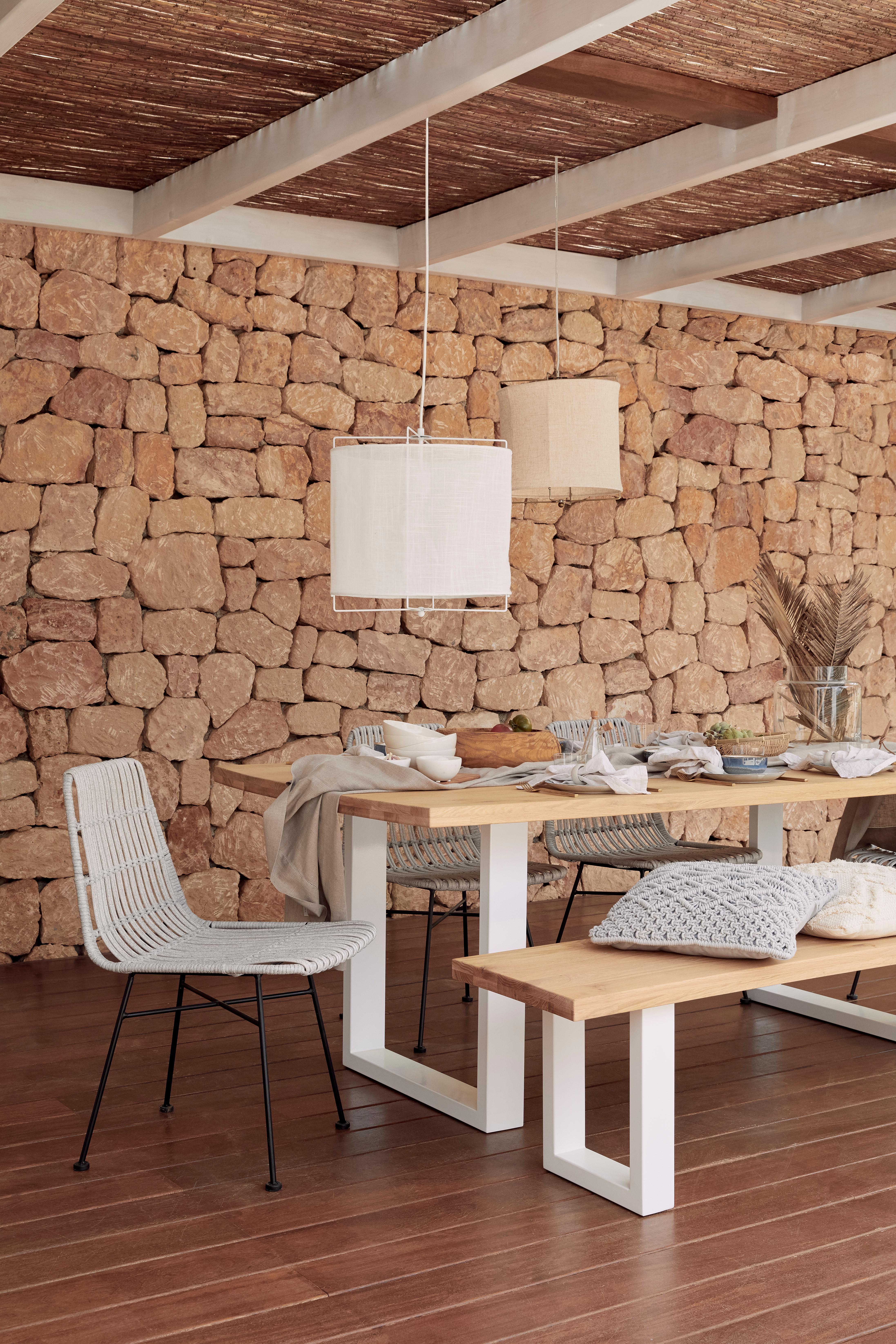 Porche con mesa y banco de madera y sillas de mimbre