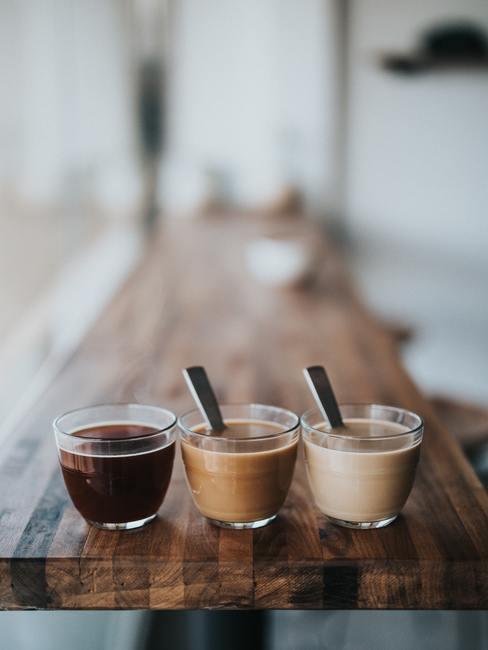 Tres tazas de café espreso marrón de varios colores encima de una encimera de madera