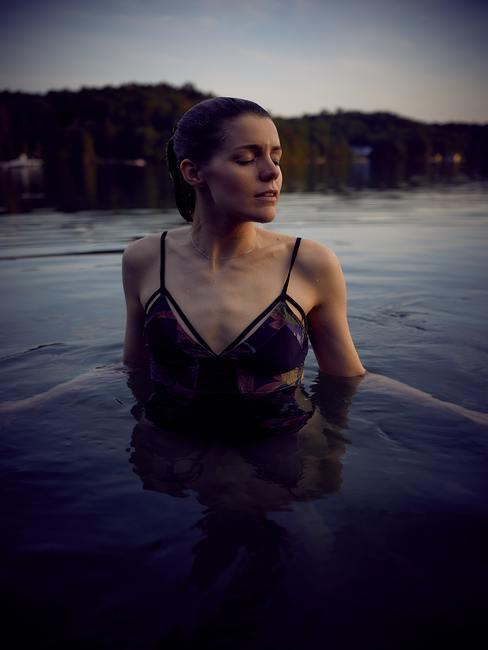 Chica en bikino saliendo del agua con los ojos cerrados