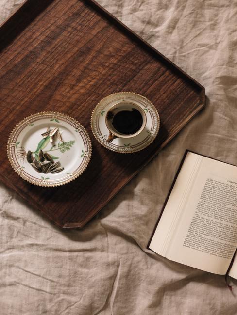 bandeja de bambú con taza de té negro junto a un libro abierto