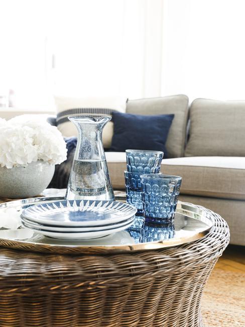 table en rotin avec une caraffe et des verres bleus