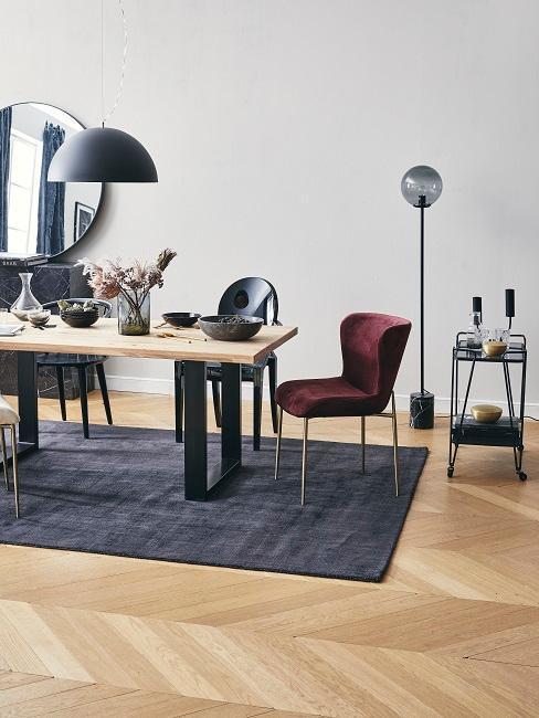 Salle à manger moderne avec table en bois et pattes en métal noir, chaises en couleurs et tapis gris foncé