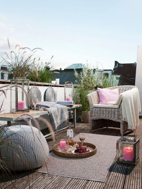 Balcon décoré des plantes, fauteuil avec plaids et coussins, un tapis crème par terre