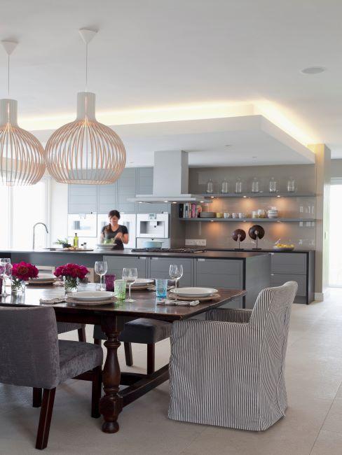 Cuisine ouverte sur salle à manger avectable en bois et chaises avec housses