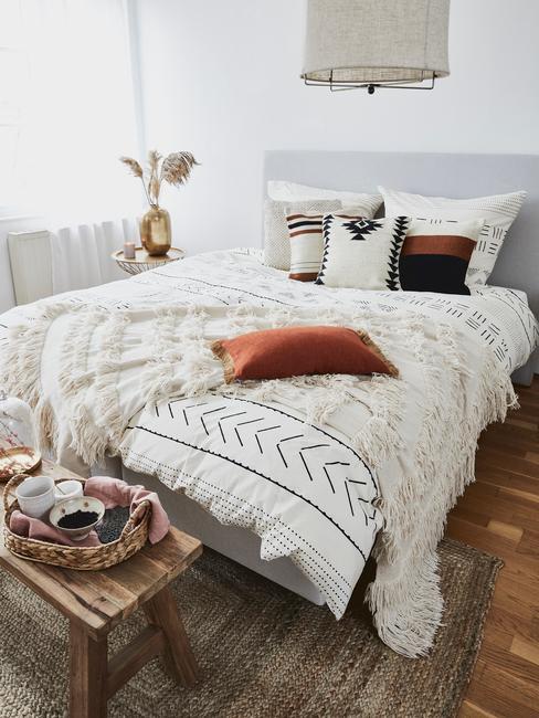 Letto ampio con coprileltto bianco e motivi orientali, cuscini e coperta con frange