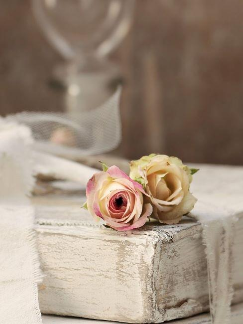 dettaglio di un mobile shabby dipinto di bianco con sopra rose secche