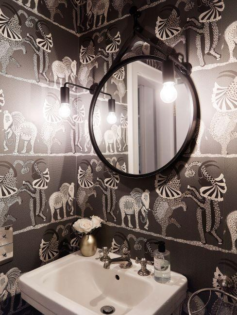 bagno con parete nera con motivi bianchi e specchio rotondo