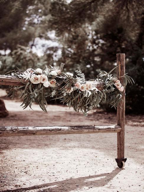 Houten hek met bloemen en trouwaccessoires