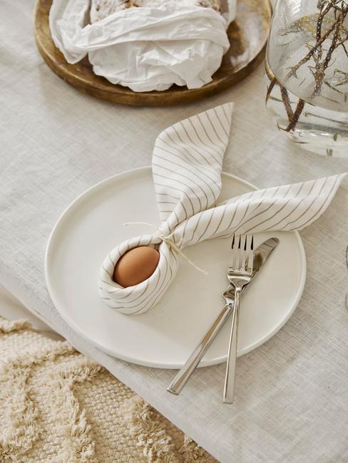 Ingezoomde tafel met wit tafelkleed en wit servies met paashaas gemaakt van een ei met servet