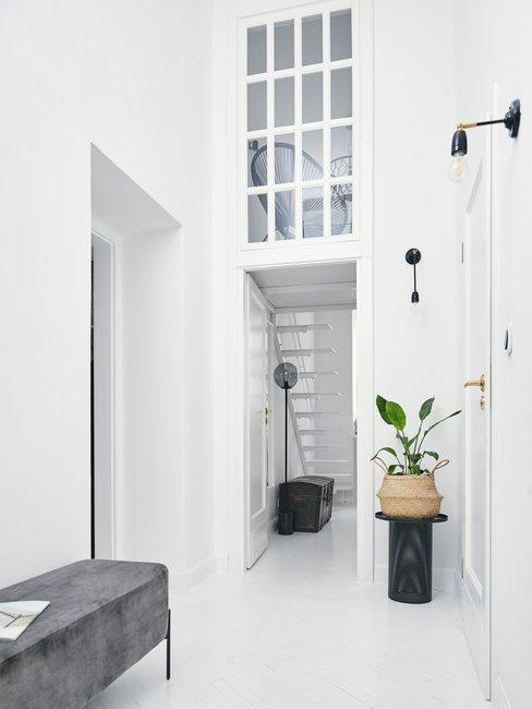 Witte ruimte en hal met grijze bank