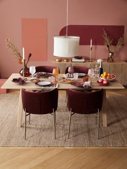 Bordeauxrode stoelen met houten tafel en witte hanglamp