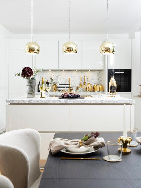 Witte keuken met houten tafel en gouden lampen boven kookeiland