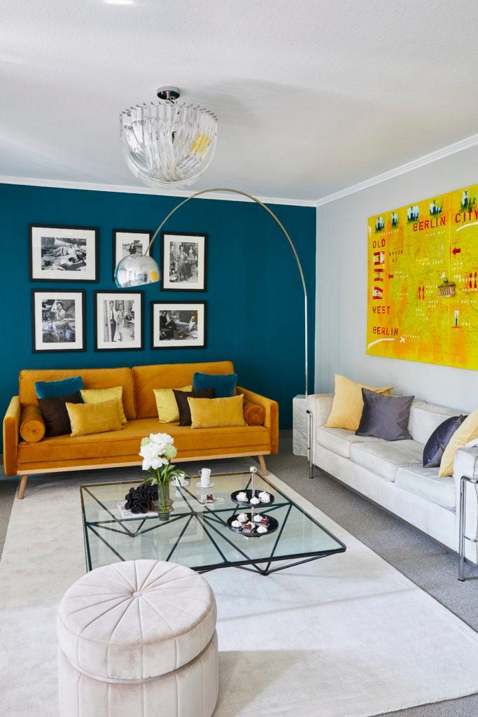 Kleurenkaart blauwe muur met oranje velvet bank met glazen salontafel op wit vloerkleed